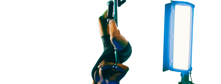 Pole Dancer on Set on All Star Stages Portable Dance Pole Upside Down Posing for the Camera with Hand on Stage Light