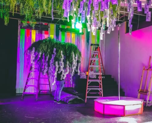 Prop money hanging from tree branches and a portable stripper pole inside neon party